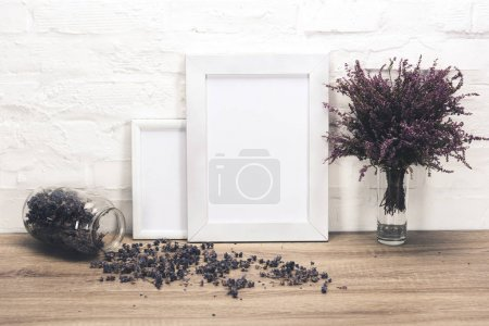 Photo for Close up view of empty photo frames and lavender flowers on wooden table - Royalty Free Image