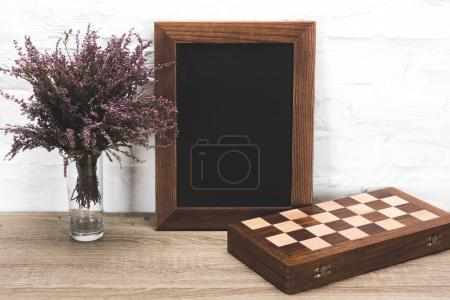 Photo frame and chess board on table
