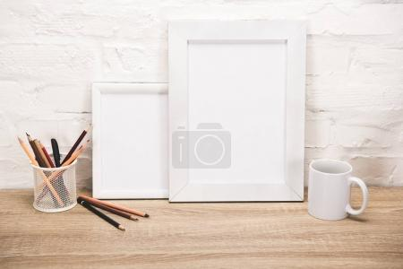 photo frames and coffee cup on tabletop