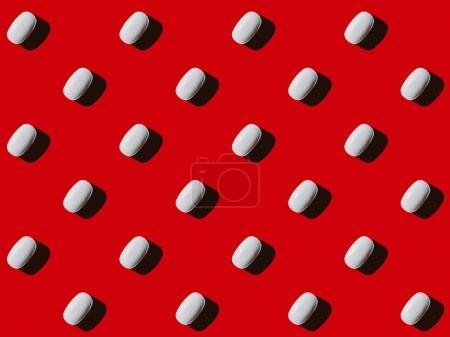Photo pour Vue rapprochée du motif réalisé à partir de capsules blanches sur rouge - image libre de droit