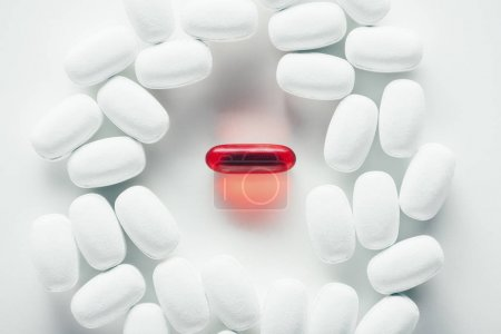 Photo for Top view of white and red medical capsules on grey - Royalty Free Image