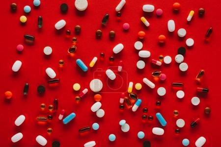 Photo pour Vue rapprochée de diverses pilules colorées sur rouge - image libre de droit