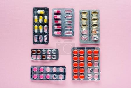 Photo pour Vue du dessus de divers médicaments en plaquettes thermoformées sur rose - image libre de droit