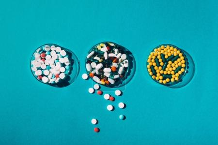 Photo for Top view of various colorful pills in petri dishes on blue - Royalty Free Image