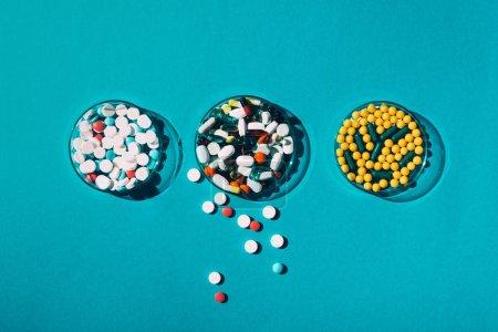 Photo pour Vue de dessus de diverses pilules colorées dans des boîtes de Pétri sur bleu - image libre de droit