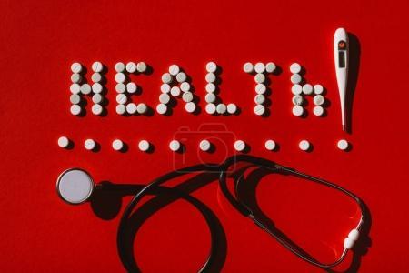 Photo pour Vue du dessus du mot santé faite de pilules, stéthoscope et thermomètre sur rouge - image libre de droit