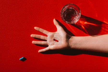 Photo for Top view of red capsule in human hand and glass of water on red - Royalty Free Image