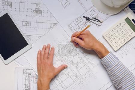 Photo for Partial view of architect working with blueprints on new building design - Royalty Free Image