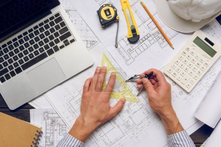 Photo for Partial view of architect with ruler and divider working on architectural project - Royalty Free Image