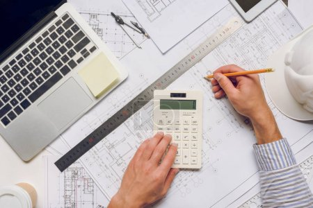 architect working with blueprints and calculator