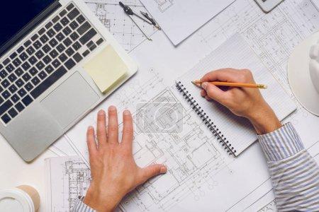 Photo pour Plan recadré de l'écriture de l'architecte dans un carnet tout en travaillant sur un projet architectural - image libre de droit