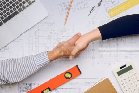 Photo for Partial view of architects shaking hands with blueprints and architect equipment on table - Royalty Free Image