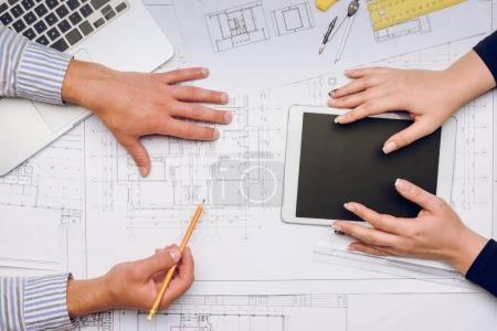 Photo pour Recadrée tir des architectes sur lieu de travail avec les bleus, ordinateur portable et tablette - image libre de droit