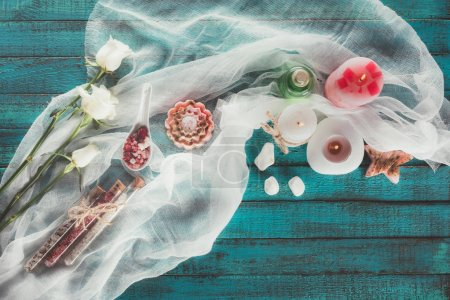 Photo for Top view of candles, soap, bathroom salt in flasks and spoon on turquoise surface - Royalty Free Image
