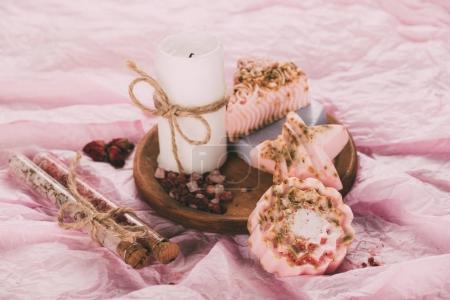 Foto de Vela hecha a mano y jabón en placa de madera, sobre superficie de color de rosa - Imagen libre de derechos
