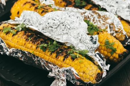 Grilled corncobs covered in foil