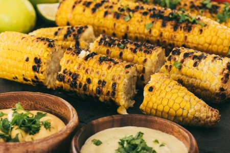 Photo for Close-up shot of grilled corn with bowls of sauce - Royalty Free Image