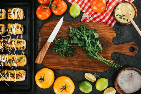 Photo for Top view of knife and dill on cutting board with various vegetables - Royalty Free Image