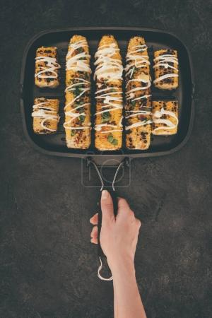 woman holding grill pan with corn