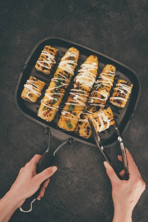 woman taking grilled corn from pan