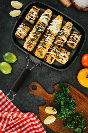 Photo for Top view of grilled corn on frying pan on kitchen table - Royalty Free Image