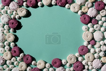 Photo for Frame of berry and white marshmallows on turquoise surface - Royalty Free Image
