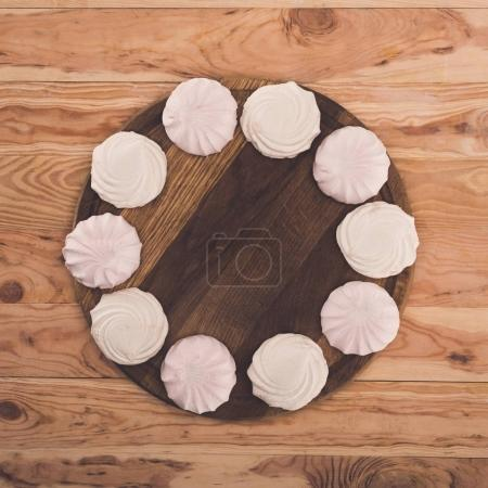 Photo for Marshmallows on round wooden board on wooden tabletop with copy space - Royalty Free Image