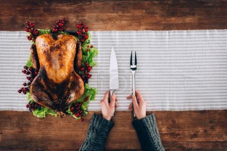 Man serving baked turkey and utensils