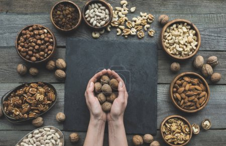 Photo for Partial top view of walnuts in human hands above slate board on wooden table - Royalty Free Image