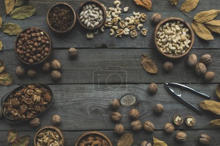 Photo for Top view of various nuts in bowls, dried leaves and nutcracker on wooden table - Royalty Free Image