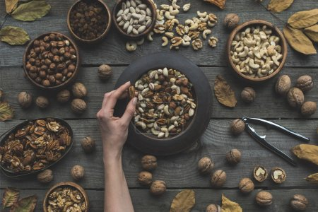 Photo for Top view of human hand and various nuts in bowls with dried autumn leaves on table - Royalty Free Image