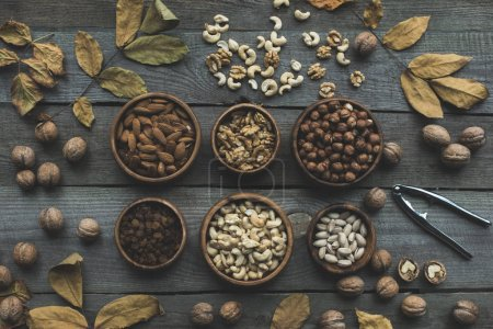 Photo for Top view of various nuts in bowls, nutcracker and dry leaves on wooden table - Royalty Free Image