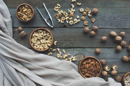 Photo pour Vue de dessus de diverses noix dans des bols, tissu et casse-noix sur table en bois - image libre de droit