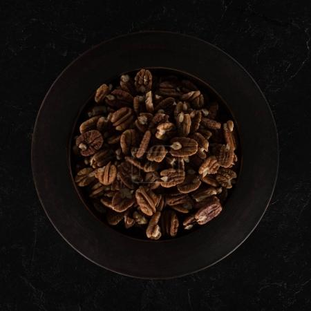Photo for Top view of delicious healthy pecan nuts in bowl on black - Royalty Free Image