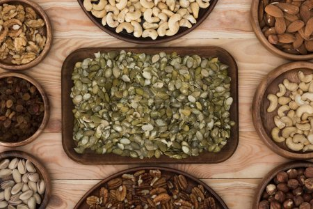 Photo for Top view of pumpkin seeds, raisins and various nuts on wooden table - Royalty Free Image