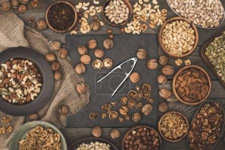 Photo for Top view of various nuts, sackcloth and nutcracker on wooden table top - Royalty Free Image