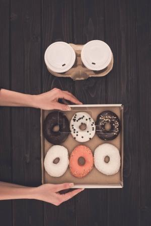 box with doughnuts in hands