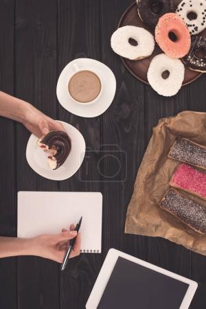 person eating donut and taking notes