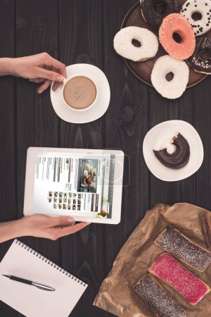 person with coffee, digital tablet and donuts