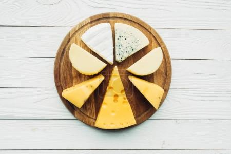 Photo for Top view of assorted various types of cheese on wooden cutting board - Royalty Free Image