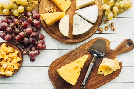 Photo for Flat lay with various types of cheese, grapes and spatula on wooden surface - Royalty Free Image
