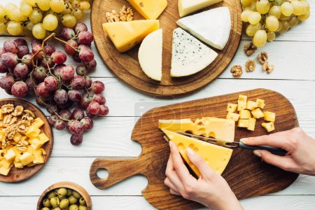 Photo for Top view with female hands cutting cheese with assorted types of cheese, grapes and olives around - Royalty Free Image
