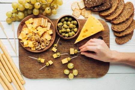 Photo for Partial view of female hand holding canape with cheese and olive - Royalty Free Image