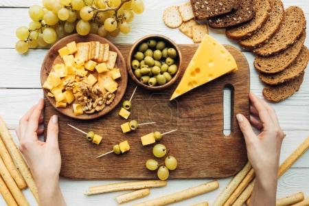 Photo for Cropped shot of female hands holding wooden cutting board with olives, cheese and canapes - Royalty Free Image