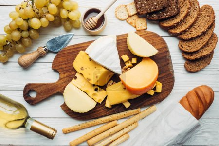 Photo for Flat lay with variety of cheese types, grapes, bottle of wine and bread on wooden surface - Royalty Free Image