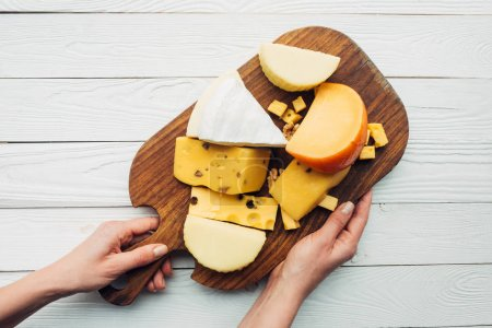 hands and assorted cheese on wooden board