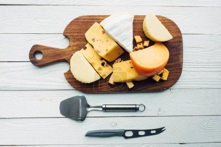 Photo pour Vue de dessus de divers types de fromage sur planche à découper et les couverts sur une surface en bois - image libre de droit