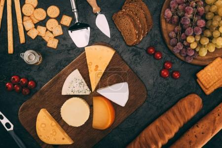 Photo for Flat lay with various cheese types, bread and grapes arranged on dark tabletop - Royalty Free Image
