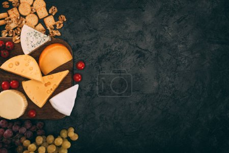 Photo for Top view of various types of cheese and cherry tomatoes on wooden cutting board with grapes on dark surface - Royalty Free Image