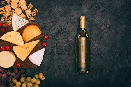 Photo for Flat lay with assorted types of cheese, grapes, cherry tomatoes and bottle of wine on dark tabletop - Royalty Free Image